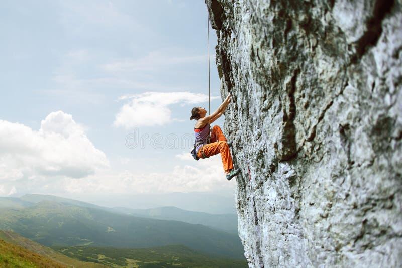 上升在峭壁的年轻亭亭玉立的女性攀岩运动员 免版税库存图片
