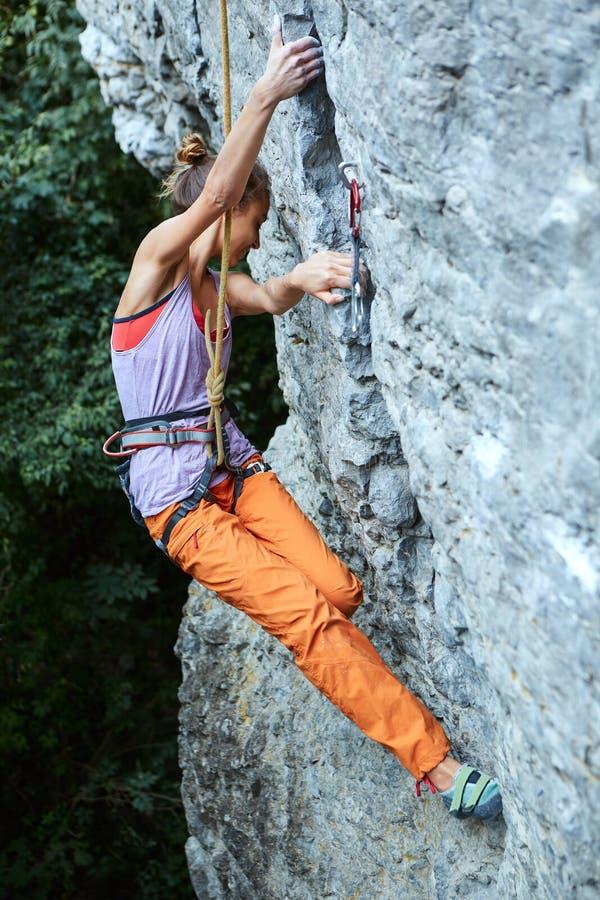 上升在峭壁的年轻亭亭玉立的妇女攀岩运动员 库存照片