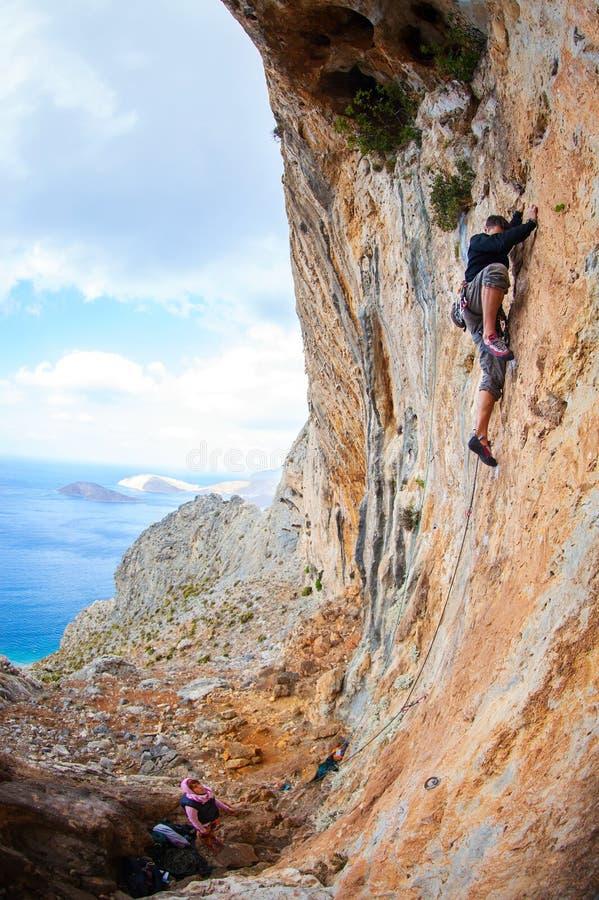 上升在峭壁的年轻人主角在海附近 免版税库存图片