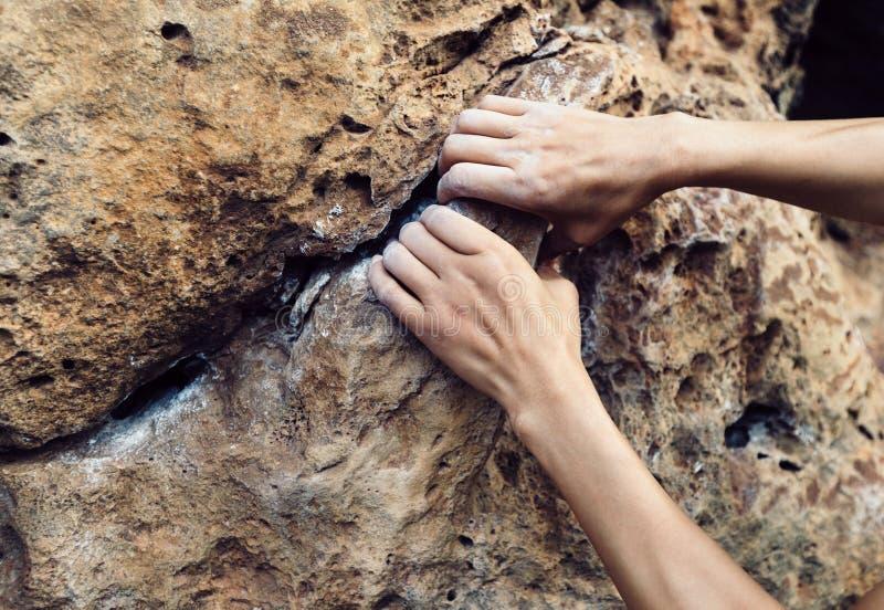 上升在峭壁边缘的登山人手 免版税库存照片
