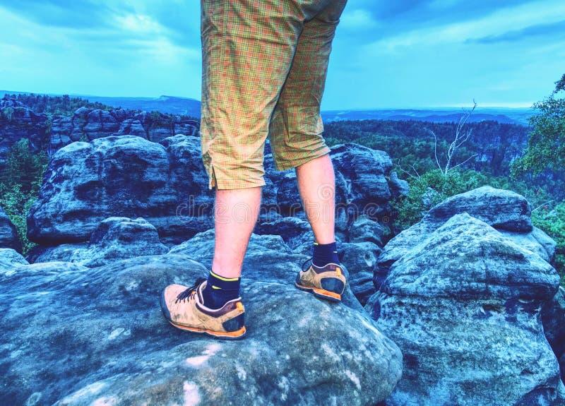 上升在日出山峰的远足者腿晃动 亭亭玉立的行程 免版税库存图片