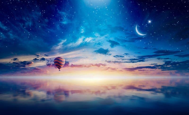 上升在日落发光的天空的平静的海上的新月形和热空气气球 库存照片