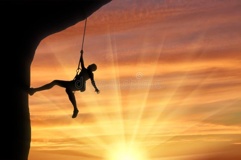 上升在日落背景的岩石的登山家 向量例证