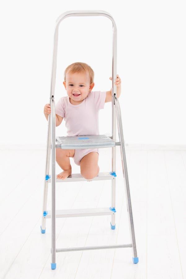 上升在梯子微笑的可爱的女婴 库存图片