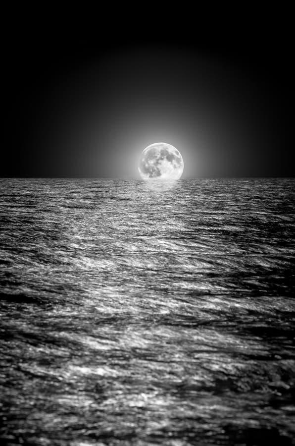 上升在海的月亮在晚上 长期风险 免版税库存照片
