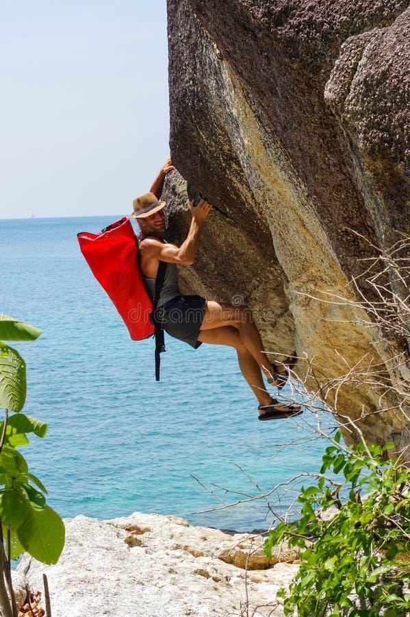 上升在海的高岩石的坚强和愉快的人有小屋红色seabag的 免版税库存图片