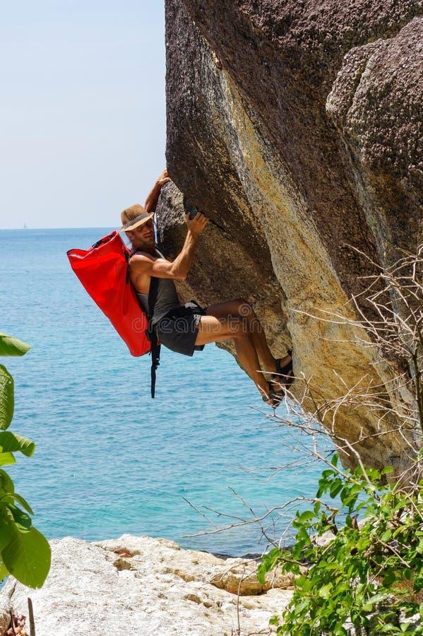 上升在海的高岩石的坚强和愉快的人有h的 免版税库存照片