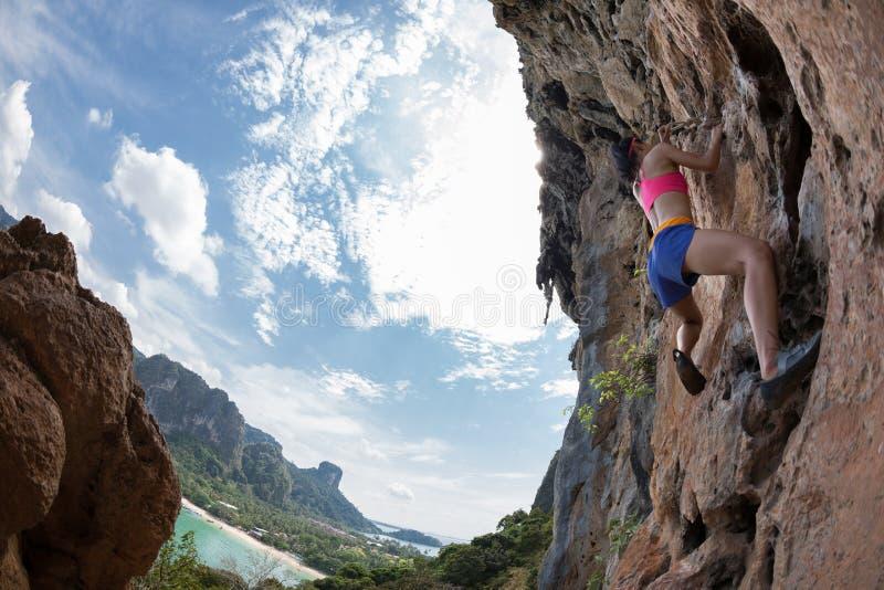 上升在海边峭壁的攀岩运动员 库存图片