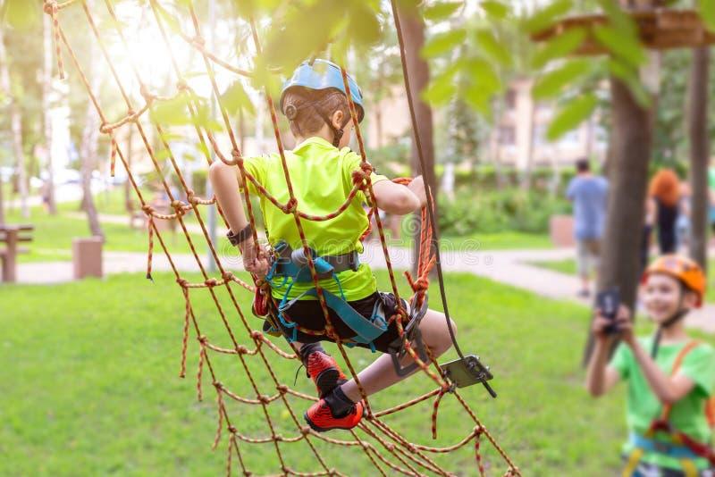 上升在绳索墙壁上的安全设备的小男孩在冒险公园 做照片的恶魔被拍摄在智能手机 儿童夏天s 免版税库存照片