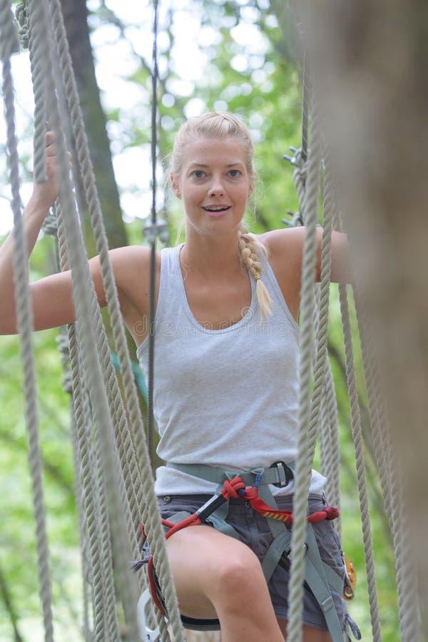 上升在绳索的逗人喜爱的女孩在冒险公园 库存图片