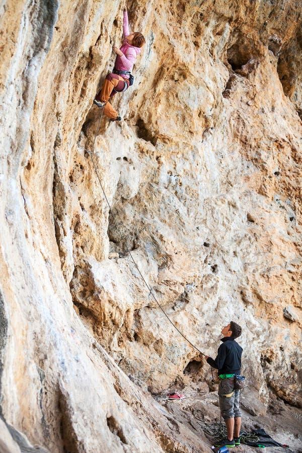 上升在自然峭壁的少妇主角 库存照片