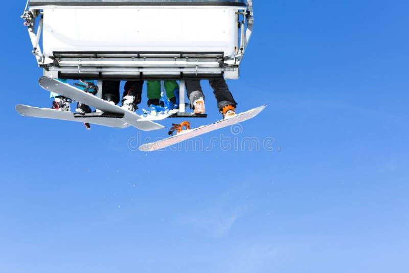 上升在驾空滑车的滑雪者反对明亮的蓝天滑雪关于 免版税库存照片