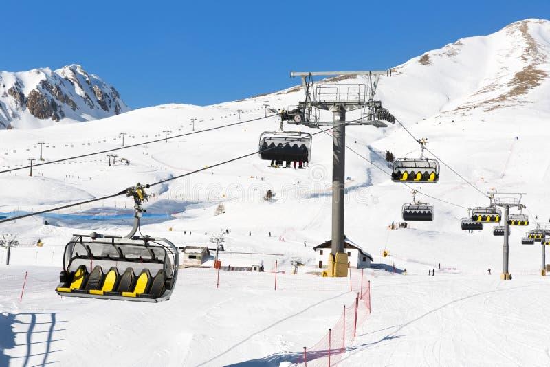 上升在驾空滑车的滑雪者反对明亮的蓝天滑雪关于 图库摄影