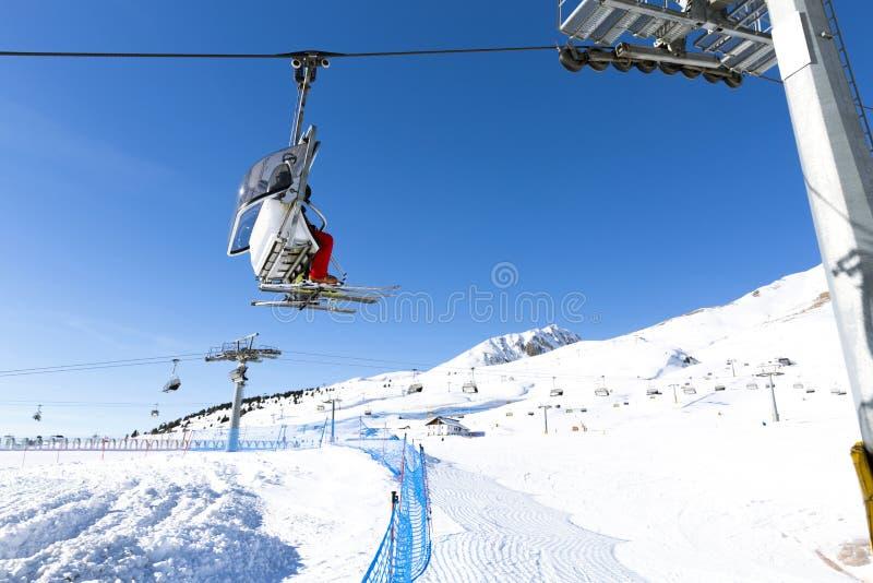 上升在驾空滑车的滑雪者反对明亮的蓝天滑雪胜地在意大利在晴朗的冬日 库存照片