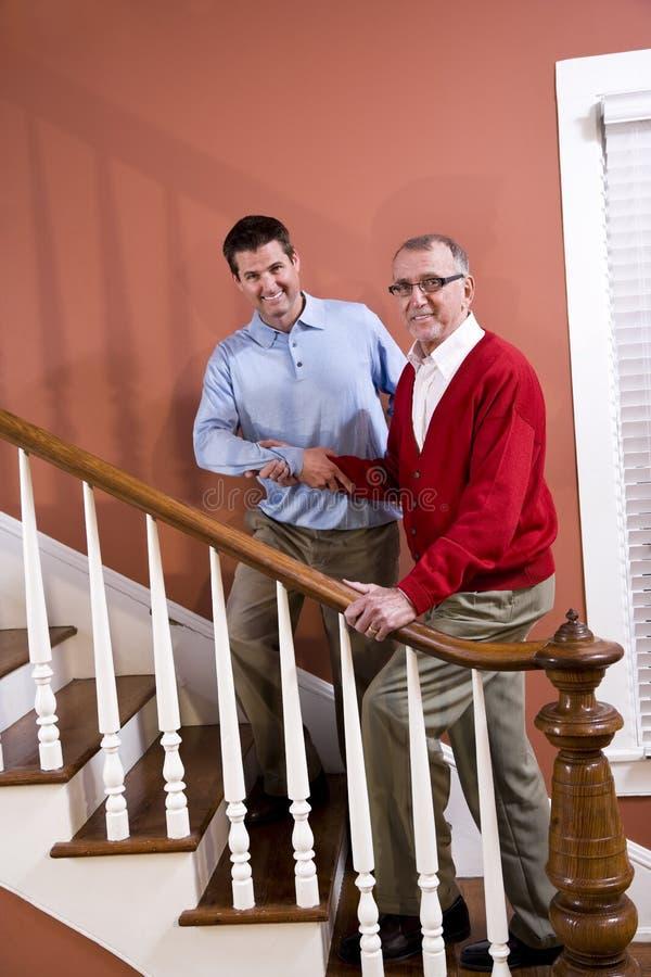 上升父亲帮助的家庭人前辈台阶 免版税图库摄影