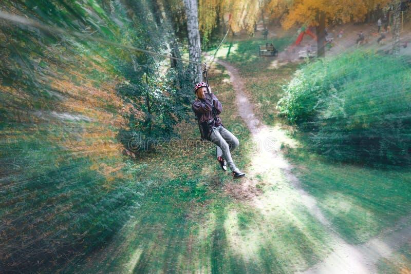 上升的齿轮在冒险公园接合攀岩或通过在绳索路,树木园,保险的障碍, 免版税库存图片