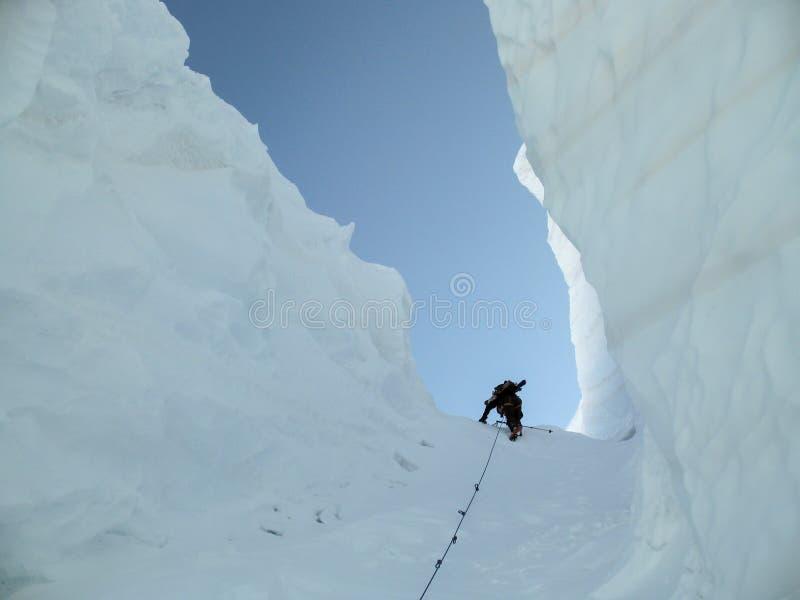 上升通过一个巨型裂隙的偏远地区滑雪者 免版税库存照片
