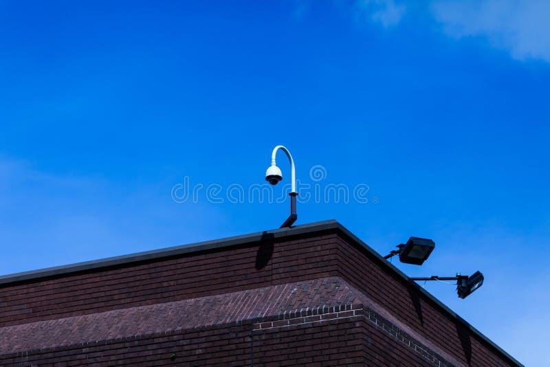上半身难看的东西葡萄酒砖瓦房一录影安全监控相机两泛光灯登上的金属边界晴朗的天空 免版税图库摄影