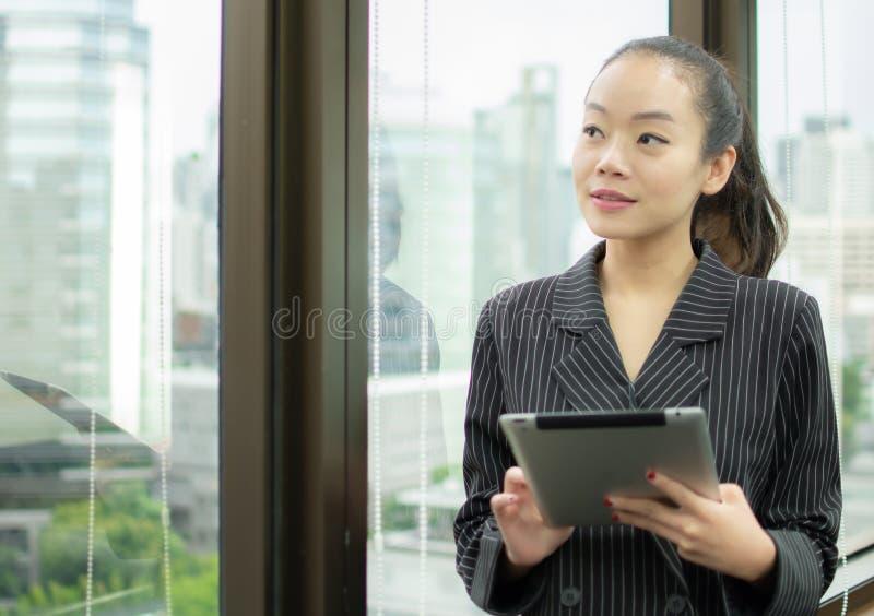 上司使用片剂和身分在窗口旁边 免版税库存照片