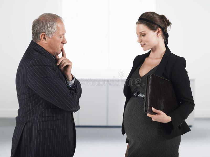 上司和怀孕的女实业家在办公室 免版税图库摄影