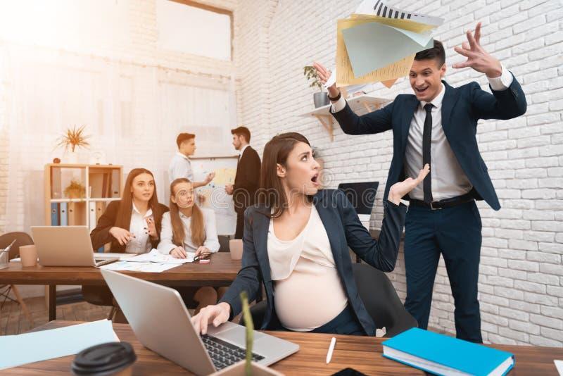 上司对年轻孕妇工作不满意 怀孕在工作 图库摄影