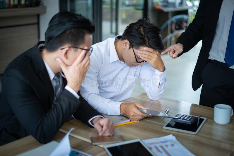 上司非常恼怒,并且呼喊对报告的销售的雇员减少,雇员被注重和在他的头的被投入的手 免版税图库摄影