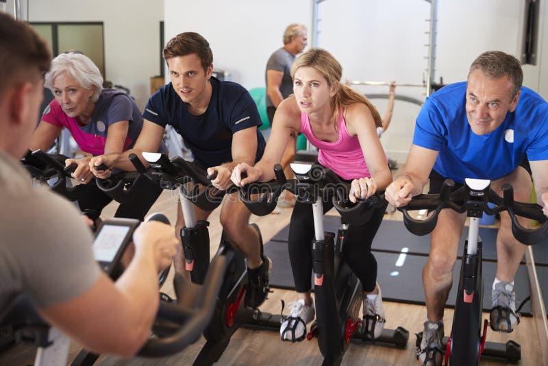 上在健身房的男性教练员旋转课 免版税库存图片