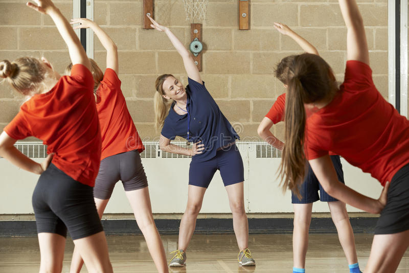 上在学校健身房的老师锻炼课 免版税库存照片