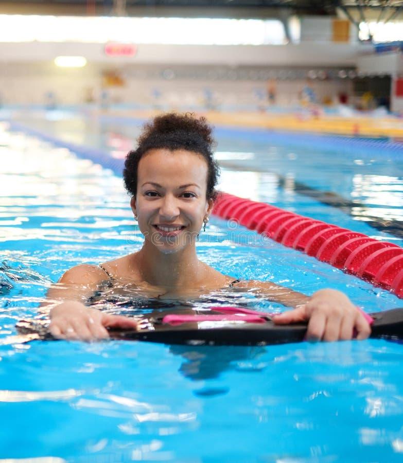 上在游泳场的黑人妇女水上体操类 免版税库存图片