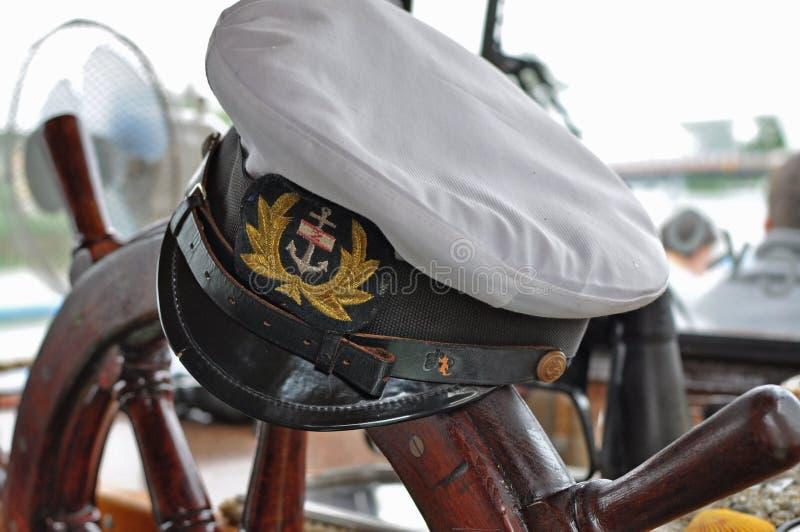 上尉的帽子和方向盘在船 免版税库存照片
