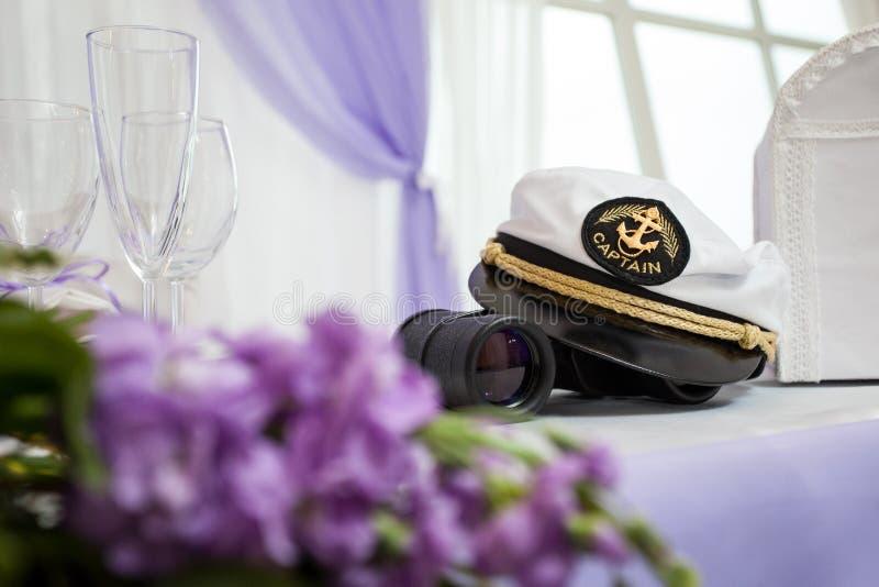 上尉的帽子在桌上的与双筒望远镜和花 免版税库存图片