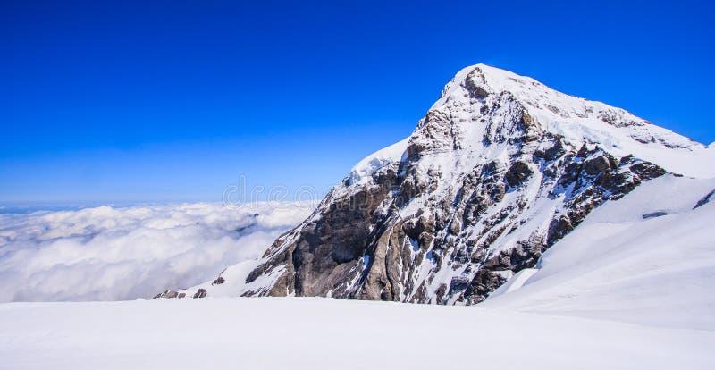 登上少女峰Jungfraujoch山顶看法有云彩和蓝天背景, Jungfraujoch火车站, Bernese Oberland 免版税库存图片