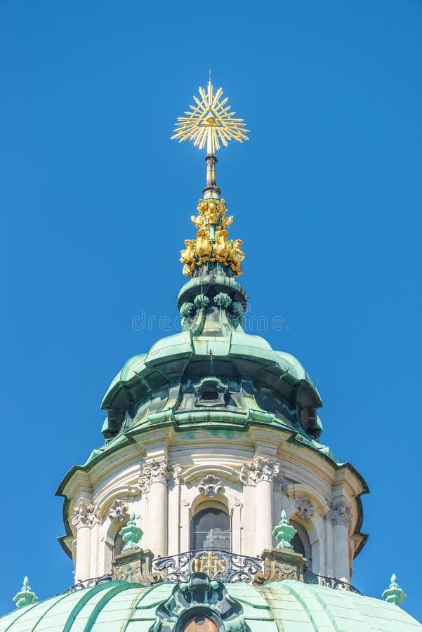 上帝的金黄眼睛圣尼古拉斯教会圆顶屋顶的在布拉格,捷克天空蔚蓝,夏天 免版税库存照片