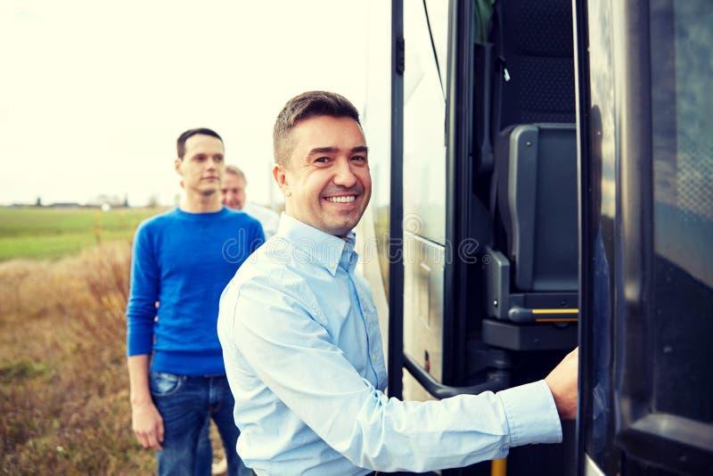 上旅行公共汽车的小组愉快的男性乘客 免版税图库摄影