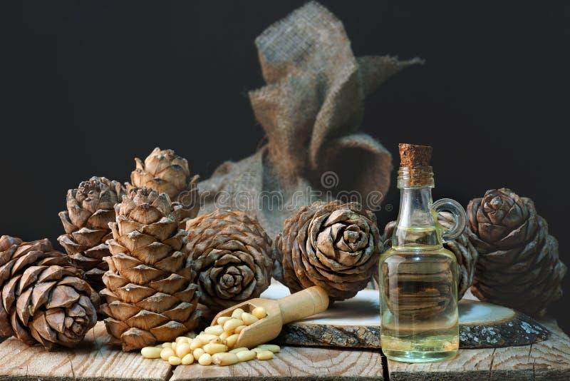 上油在杉木锥体和坚果围拢的一个玻璃瓶在一张木桌上,在黑暗的背景后 库存图片