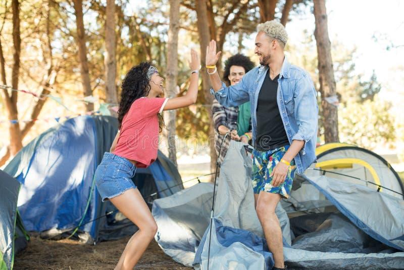 给上流五的愉快的年轻朋友,当设定帐篷时 免版税库存照片