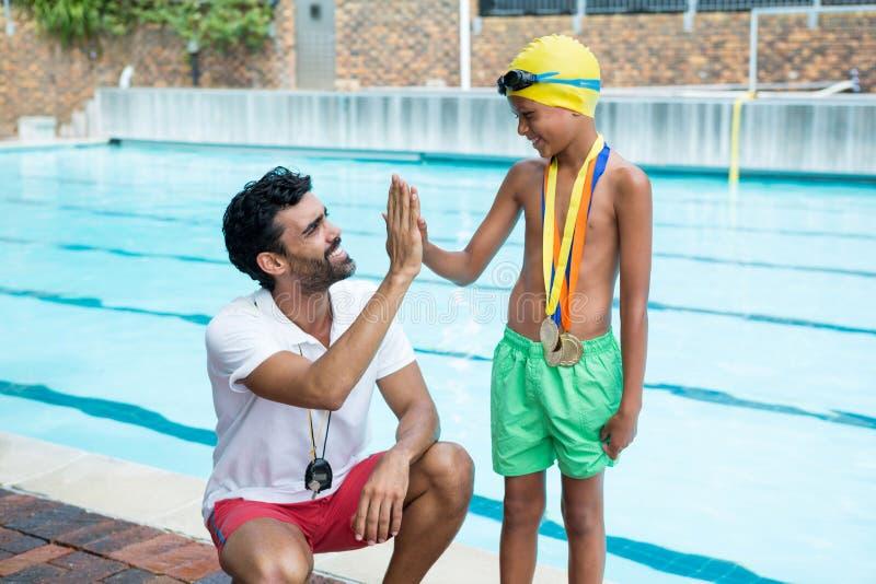 给上流五的男孩教练在游泳池边附近 免版税库存图片