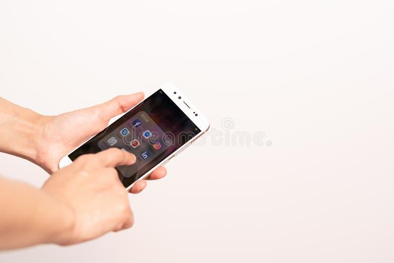 上海,中国-, 2018年:妇女递有社会媒介,智能手机生活方式象的感人的智能手机屏幕  免版税库存图片