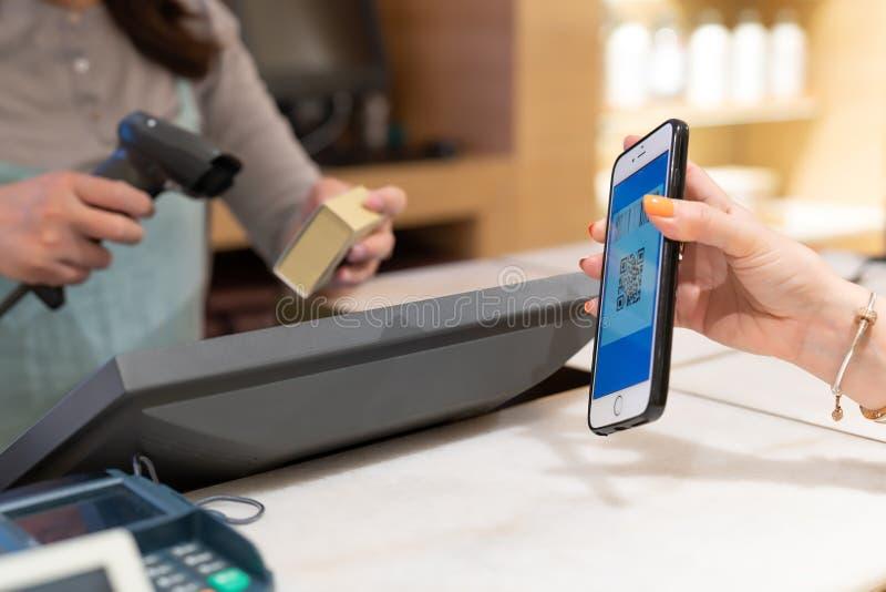 上海,中国-, 2018年:Qr代码付款,网上购物,妇女手举行付款的智能手机 免版税图库摄影