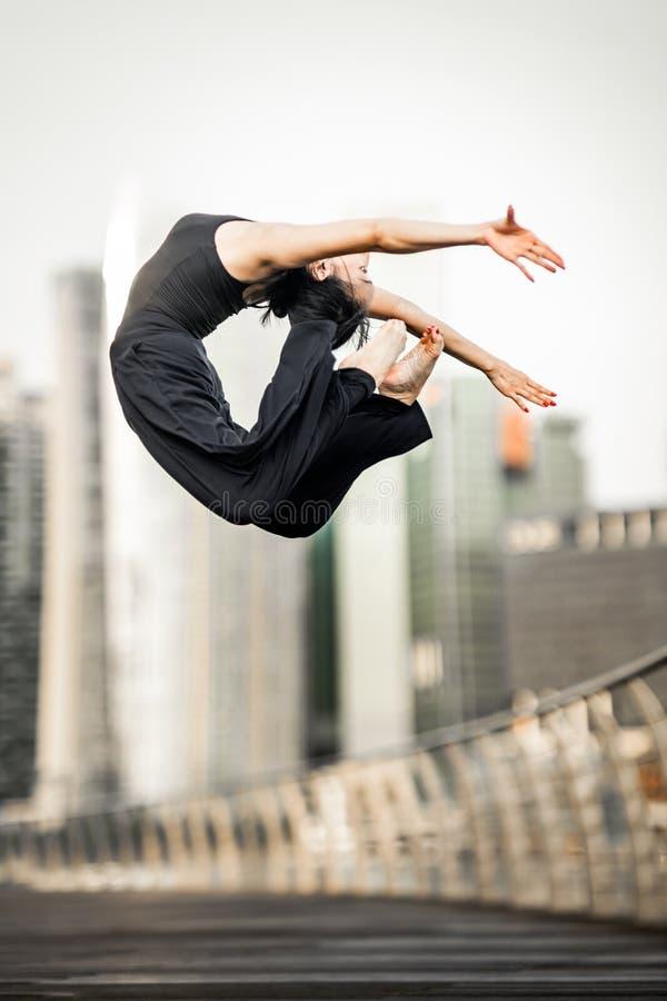 上涨 热情的少妇运动员执行一个完善的飞跃h 库存照片