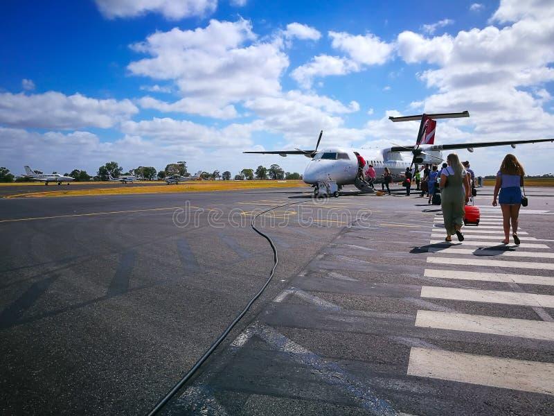 上澳大利亚航空公司国内航空公司飞机型号的人们:De Havilland Dhc-8-300破折号8/8q在鲜绿色机场 库存照片