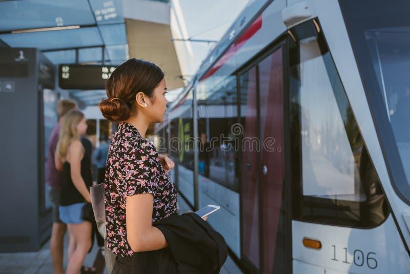 上火车的年轻亚裔女实业家在她的工作期间通勤 免版税库存照片