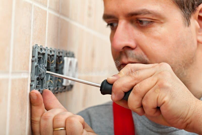 登上电子墙壁装置的电工 免版税库存照片