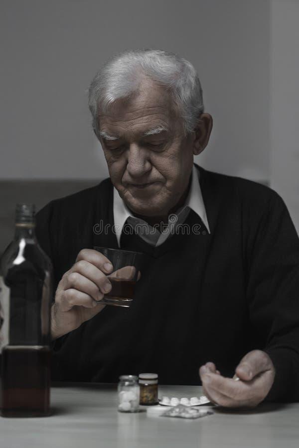 上瘾的退休人员饮用的威士忌酒 免版税图库摄影