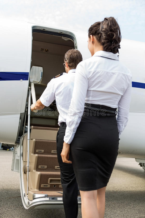 上私人喷气式飞机的空中小姐和飞行员 免版税图库摄影