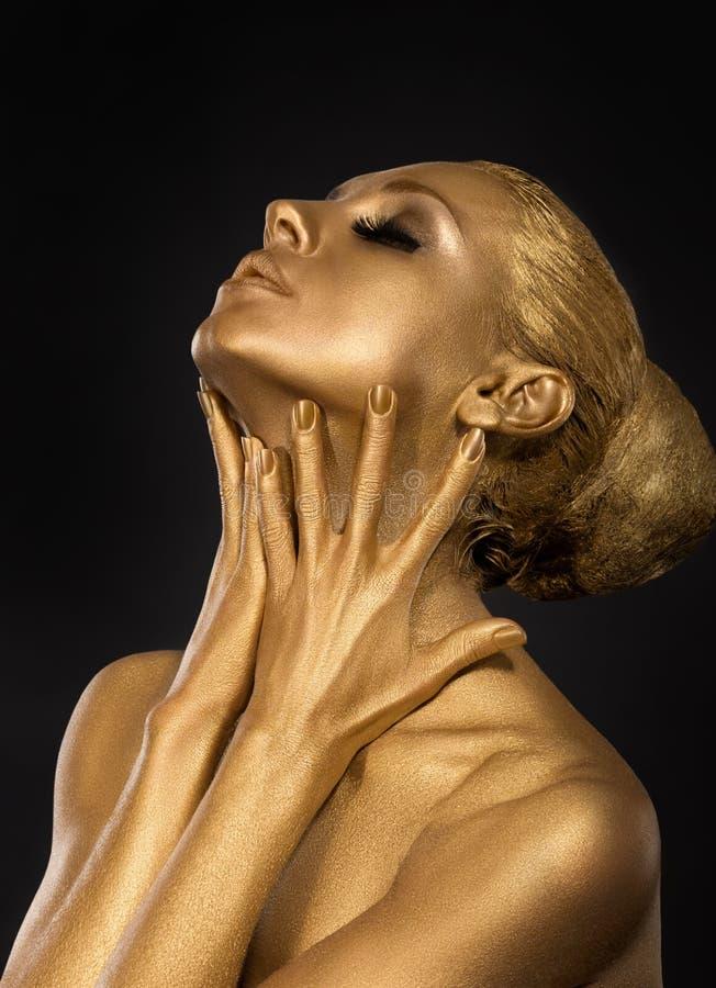 上色。 镀金面。 金黄被镀的妇女的面孔。 艺术概念。 被镀金的身体。 在她的手的焦点 免版税库存照片