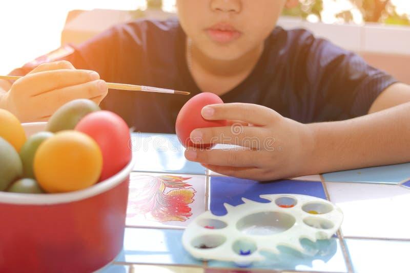 上色与油漆刷的小男孩复活节彩蛋 阳光作用 葡萄酒口气 免版税图库摄影