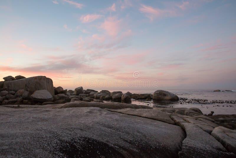 上色云彩形成在水的日落与岩石 免版税库存照片