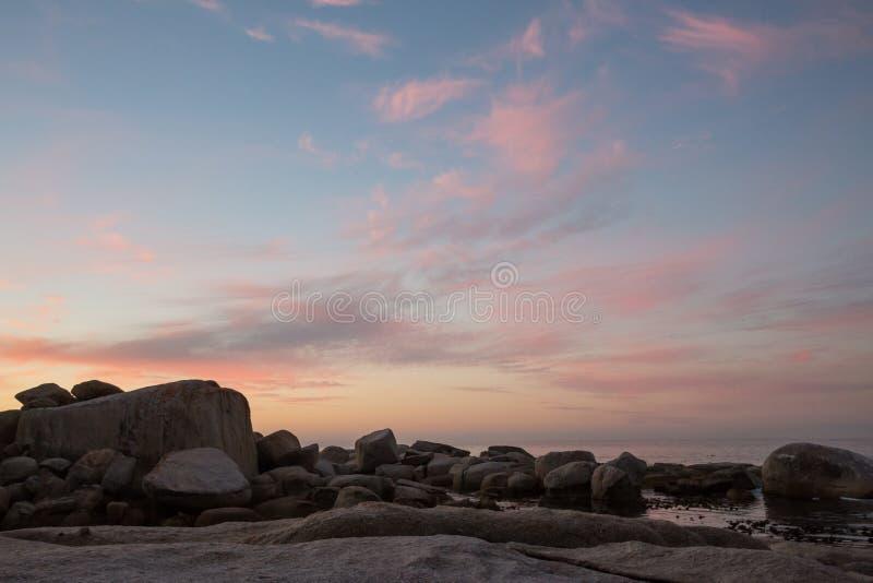 上色云彩形成在水的日落 免版税图库摄影