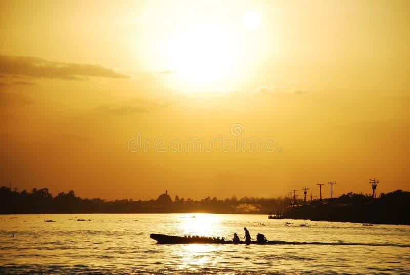 上色人的图片一条小船的在河在日落 免版税库存图片